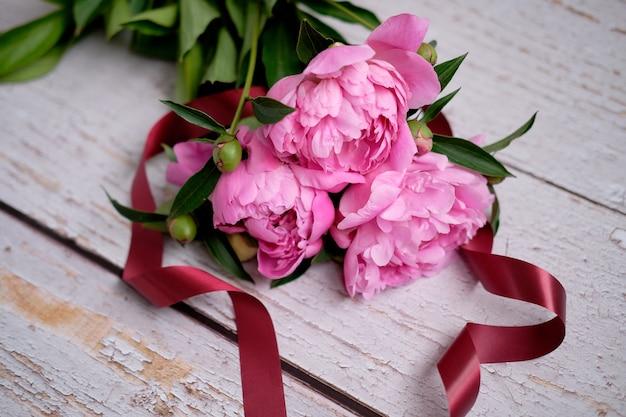 Een boeket roze pioenrozen op een donkere houten ondergrond