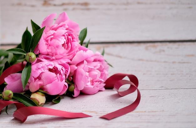 Een boeket roze pioenrozen op een lichte houten ondergrond