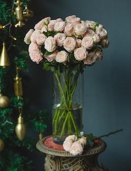 Een boeket roze rozen en een enkele tak van roos met groene bladeren in een vaas