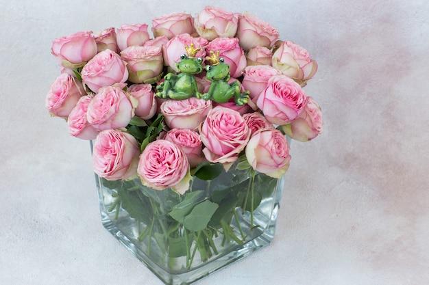 Een boeket roze rozen in een doorzichtige vierkante vaas en twee beeldjes van kikkers