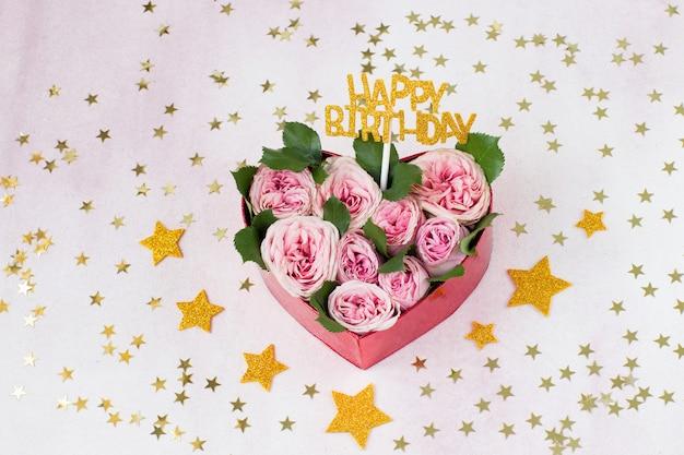 Een boeket roze rozen in een geschenkdoos in de vorm van een hart en een sticker met het opschrift happy birthday