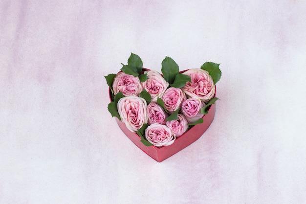 Een boeket roze rozen in een geschenkdoos in de vorm van een hart