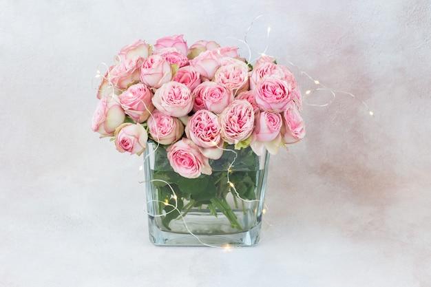 Een boeket roze rozen in een transparante vierkante vaas en een slinger van lichtjes