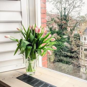 Een boeket roze tulpen in een glazen vaas op een raam met open luiken