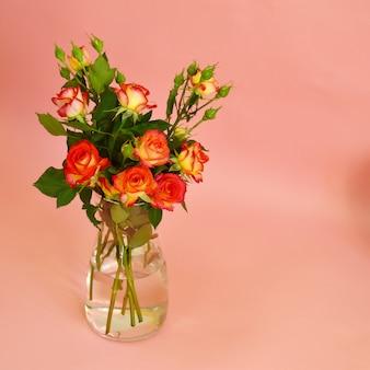 Een boeket rozen in glazen vaas op roze achtergrond.