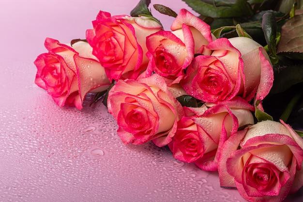 Een boeket rozen voor de vakantie. vrouwendag, valentijnsdag, naamdag. op een roze achtergrond met reflectie. kopieer ruimte