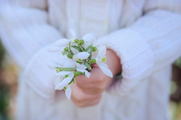 Een boeket sneeuwklokjes in de handen van een klein meisje. eerste lentebloemen. pasen
