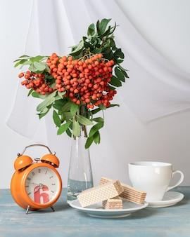 Een boeket takken met rode lijsterbessen, een wekker, een witte kop en wafels op een wit bord op tafel, lichtsleutel, verticaal frame. ochtend herfst ontbijt. ontbijt voor dierbaren