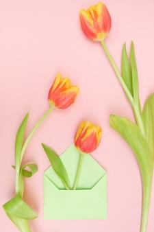 Een boeket tulpen en een envelop met een notitie op een zacht roze achtergrond. concept van internationale vrouwendag, moederdag, pasen