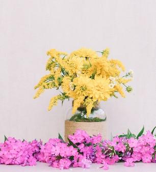 Een boeket van bloemenchrysanten, guldenroede en madeliefjes in een vaas onder de flox op een roze achtergrond. getinte foto