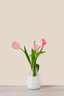 Een boeket van drie roze tulpen staat in een glazen vaas met kant. het concept van het lentefeest