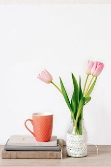 Een boeket van drie roze tulpen staat in een glazen vaas met kant