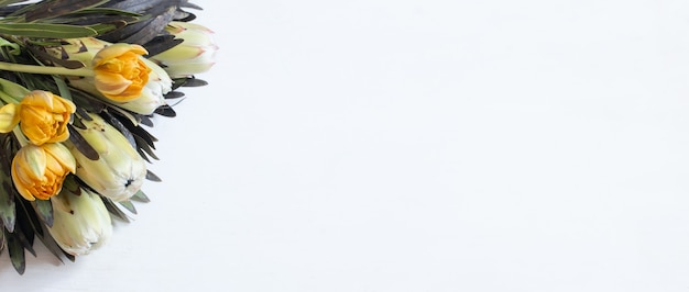 Een boeket van exotische bloemen protea en tulpen voor de vakantie bovenaanzicht. bloembezorging en feestelijk boeketconcept.