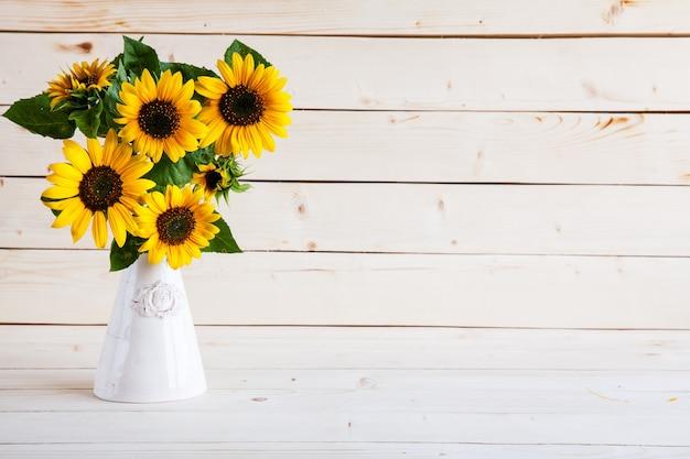 Een boeket van herfst zonnebloemen in een vaas op een grungy houten tafel.