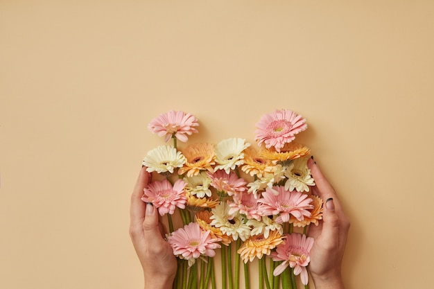 Een boeket van kleurrijke gerbera's meisje houdt in handen op een gele papieren achtergrond. lente samenstelling. als ansichtkaart voor moederdag of 8 maart. plat gelegd
