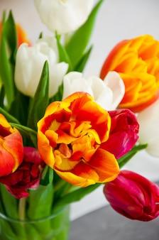 Een boeket van kleurrijke natuurlijke tulpen in een glazen vaas met water op een betonnen achtergrond. moederdag wenskaart, vrouwendag. verticale oriëntatie. detailopname.