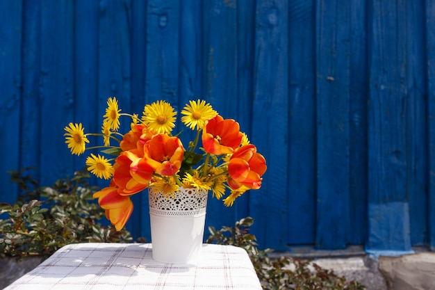 Een boeket van lentebloemen in een witte vaas op een blauwe houten achtergrond.