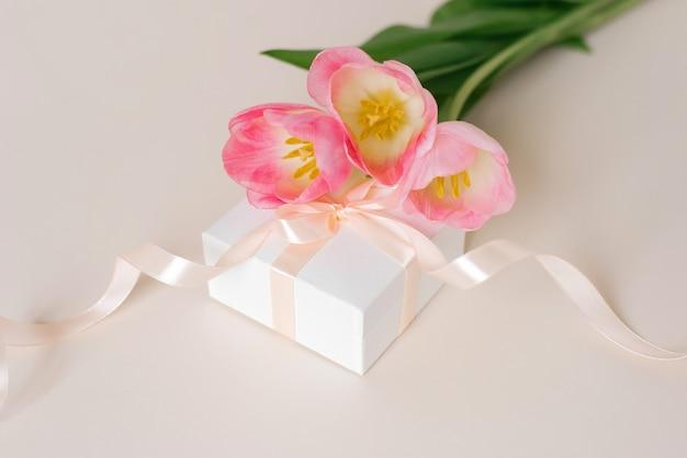 Een boeket van mooie tulpen en een geschenk op een bovenaanzicht van een beige achtergrond. moederdagachtergrond, valentijnsdag, internationale vrouwendag. vakantie, geef een cadeau.