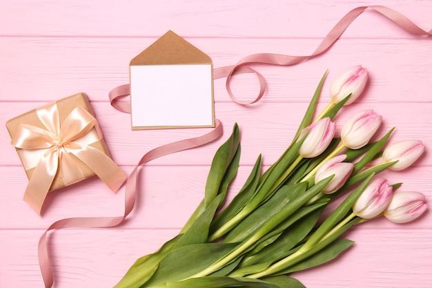 Een boeket van mooie tulpen en een geschenk op een houten achtergrond bovenaanzicht
