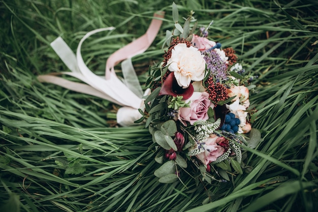 Een boeket van rode bloemen, zwarte bessen en groen. het boeket van de bruid