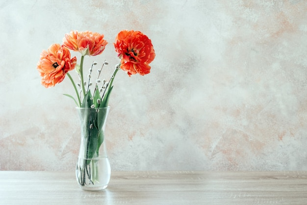 Een boeket van rode dubbele tulpen in een vaas de lente bloeit pasen en de dagachtergrond van vrouwen
