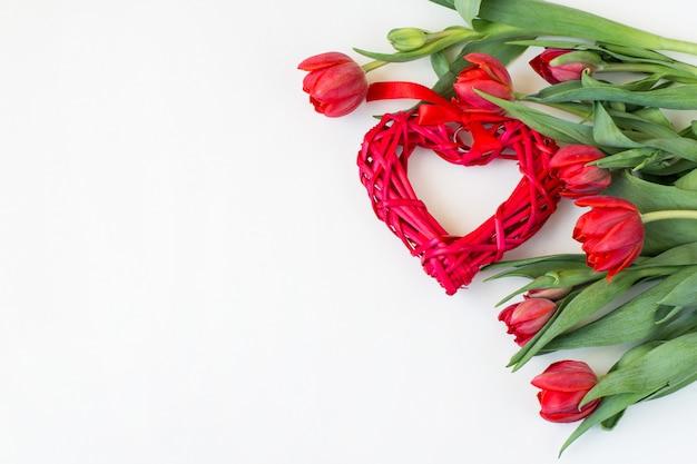 Een boeket van rode tulpen en een rieten rood hart