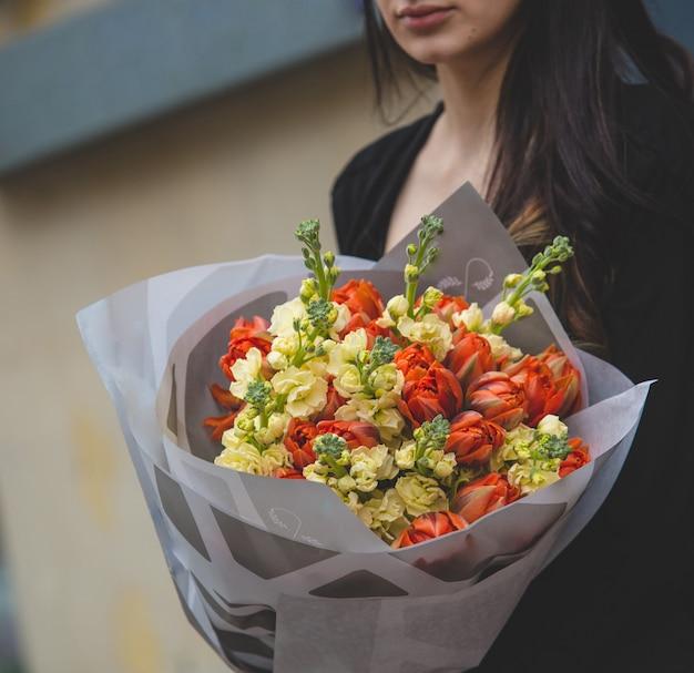Een boeket van rode tulpen en gele pioenrozen die worden vastgehouden door een vrouw in het zwart