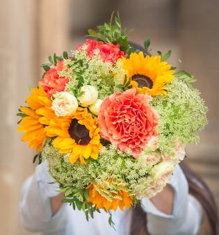 Een boeket van roze bloemen en gele zonnebloemen met groene bladeren