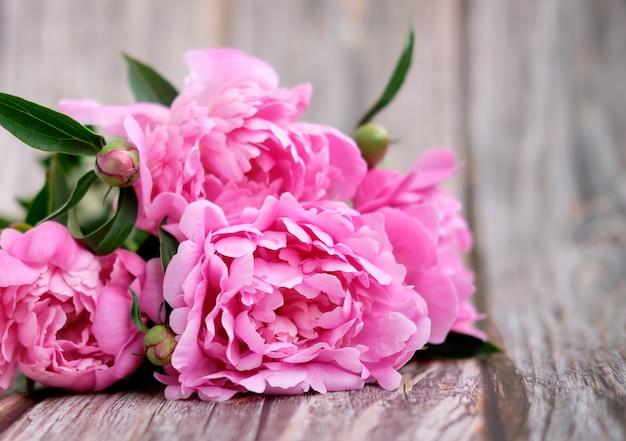 Een boeket van roze pioenrozen op een lichte houten achtergrond close-up