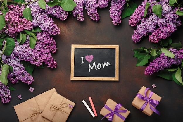 Een boeket van seringen met schoolbord, geschenkdoos, ambachtelijke envelop op roestige achtergrond. moederdag