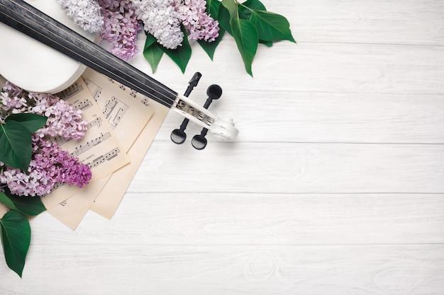 Een boeket van seringen met viool en muziek blad op een witte houten tafel. bovenkant wiev met ruimte voor uw tekst.