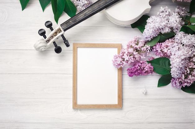 Een boeket van seringen met viool, schoolbord en muziek blad op een witte houten tafel. bovenkant wiev met ruimte voor uw tekst