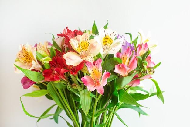 Een boeket van veelkleurige bloemen op een grijze muur zijaanzicht