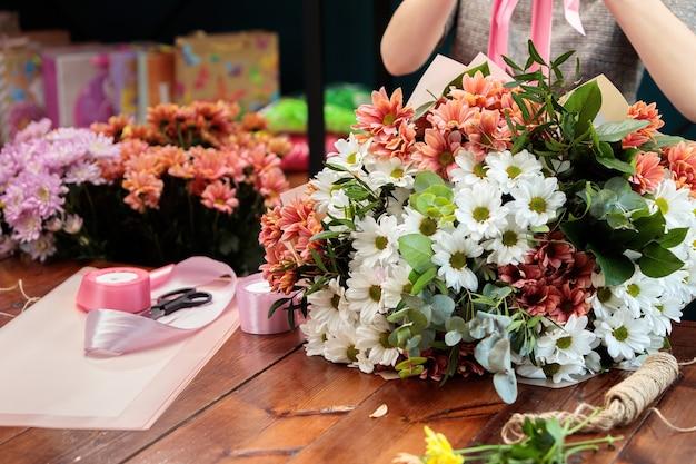 Een boeket van veelkleurige chrysanten ligt op een houten tafel. het proces van het maken van een boeket bloemen door een bloemist.