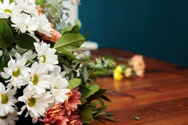 Een boeket van veelkleurige chrysanten ligt op een houten tafel.