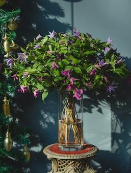 Een boeket van violette bloemen met groene bladeren in een vaas