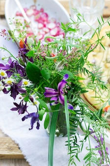 Een boeket van wilde bloemen, gebakken radijs en focaccia op een houten tafel. rustieke stijl, selectieve aandacht.