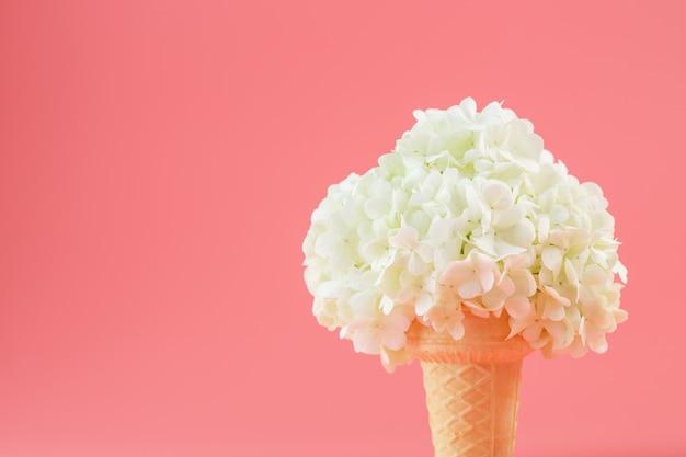 Een boeket van witte bloemen in een ijsje op roze.