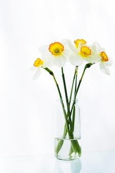 Een boeket van witte narcissenbloemen bevindt zich in een kruik water op een lijst