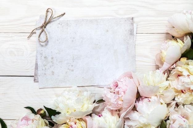 Een boeket van witte pioenrozen op een houten achtergrond. plaats voor tekst.