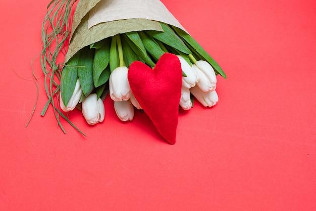 Een boeket van witte tulpen en een rood fluwelen hart op een rode tafel - het concept van valentijnsdag.