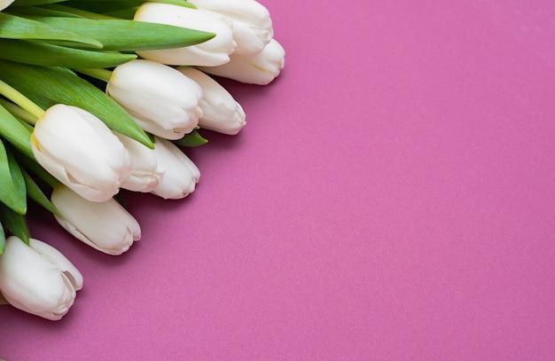 Een boeket van witte tulpen en een rood fluwelen hart op een roze achtergrond - het concept van valentijnsdag.