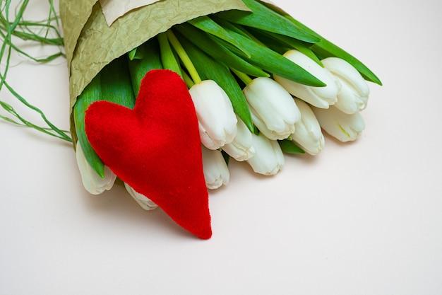 Een boeket van witte tulpen en een rood fluwelen hart op een witte tafel