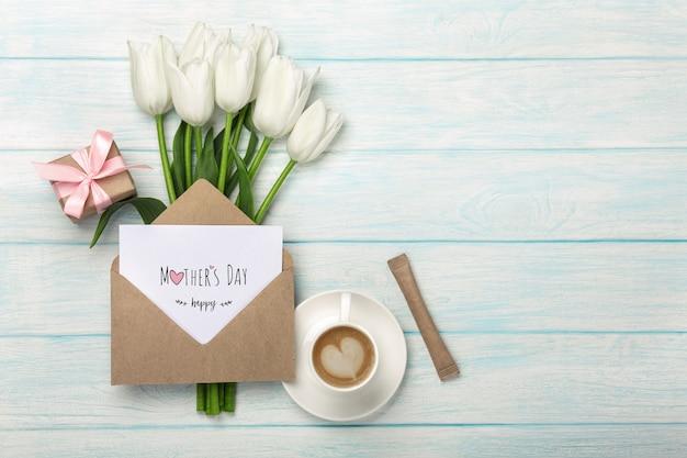 Een boeket van witte tulpen, kopje koffie, geschenkdoos met een liefdesbrief en envelop op blauwe houten planken. moederdag