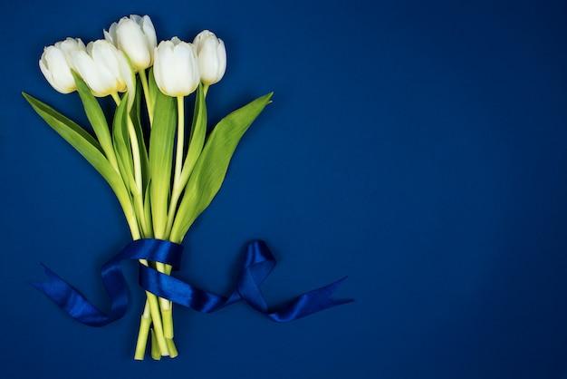 Een boeket van witte tulpen vastgebonden met een lint. op een blauwe achtergrond. briefkaart voor valentijnsdag en 8 maart