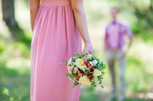 Een boeket verse bloemen in handen nesta in een roze jurk close-up