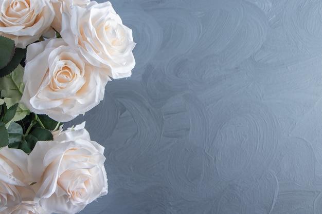 Een boeket witte bloemen in een emmer, op de witte tafel.