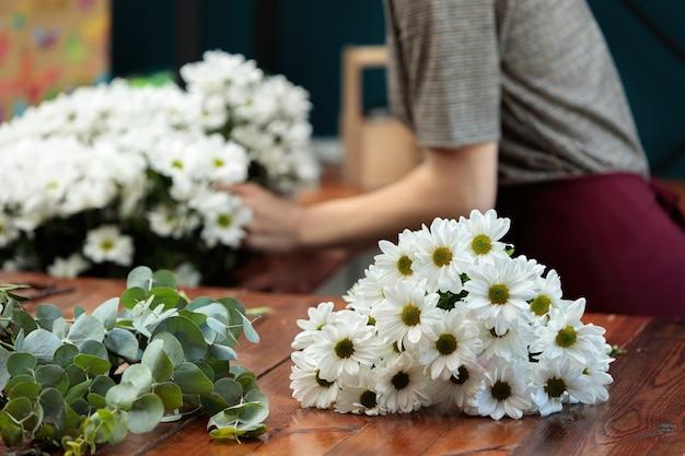 Een boeket witte chrysanten ligt op een houten tafel.