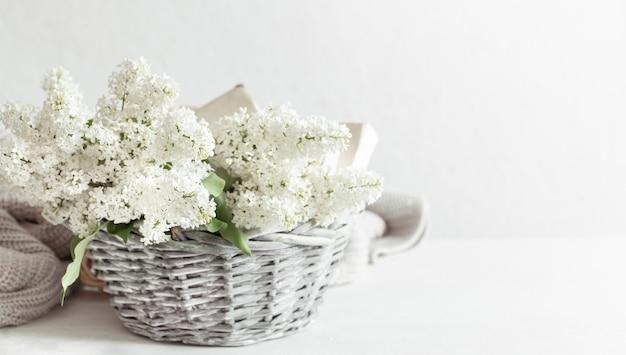 Een boeket witte lila bloemen in een decoratieve mand op een lichttafel
