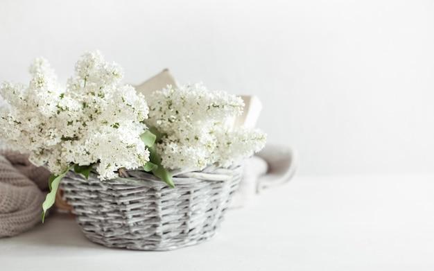 Een boeket witte lila bloemen in een decoratieve mand